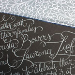Christa and Lawrence: wedding invitation featuring custom calligraphy in white foil on 2 ply charcoal card stock and envelope liner in pewter with white floral pattern